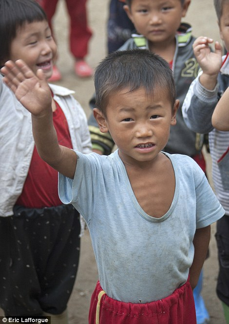 A malnourished North Korean boy photographed by Eric Lafforgue.