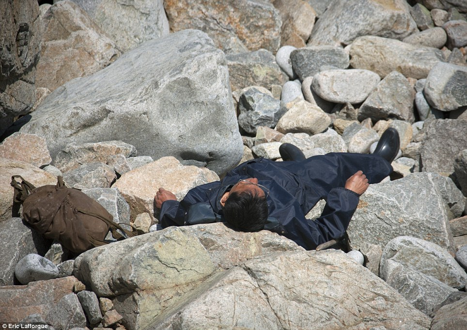 A North Korean man resting on rocks photographed by Eric Lafforgue.