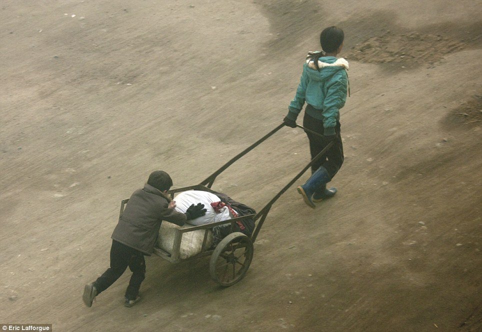 A woman pulling a cart in North Korea, photographed by Eric Lafforgue.