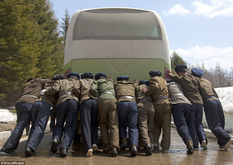 North Korea doesn't allow any photographs of soldiers to be taken. Especially when soldiers are pushing a broken down bus.